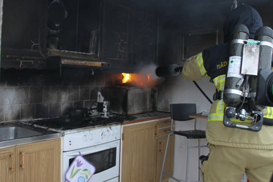 Firefighter putting out a fire in the kitchen